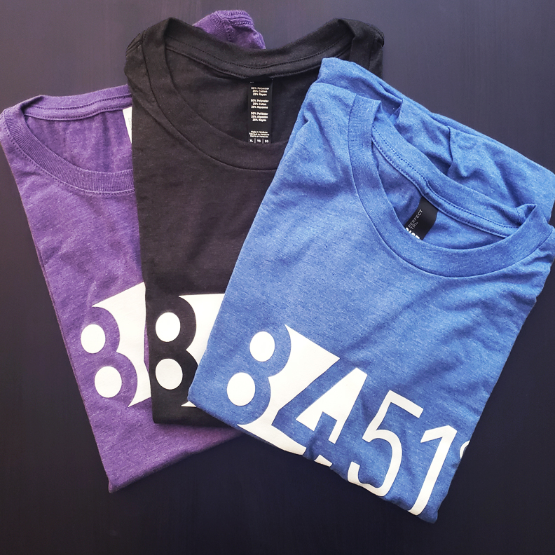 A blue, black, and purple folded tshirt with a white 84.51 logo screen printed on it.
