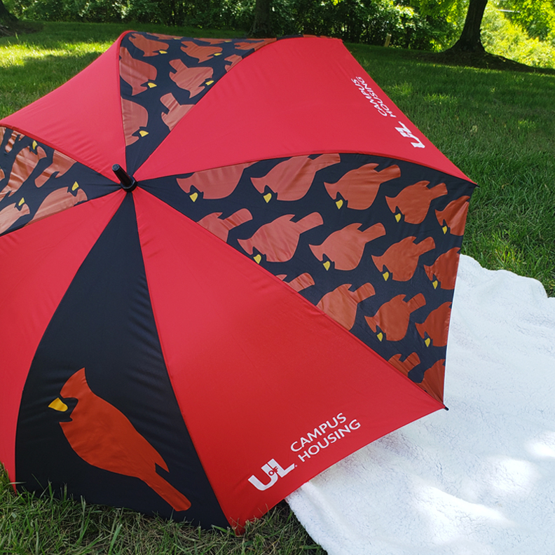 A University of Lousiville red and black umbrella sits in the grass.