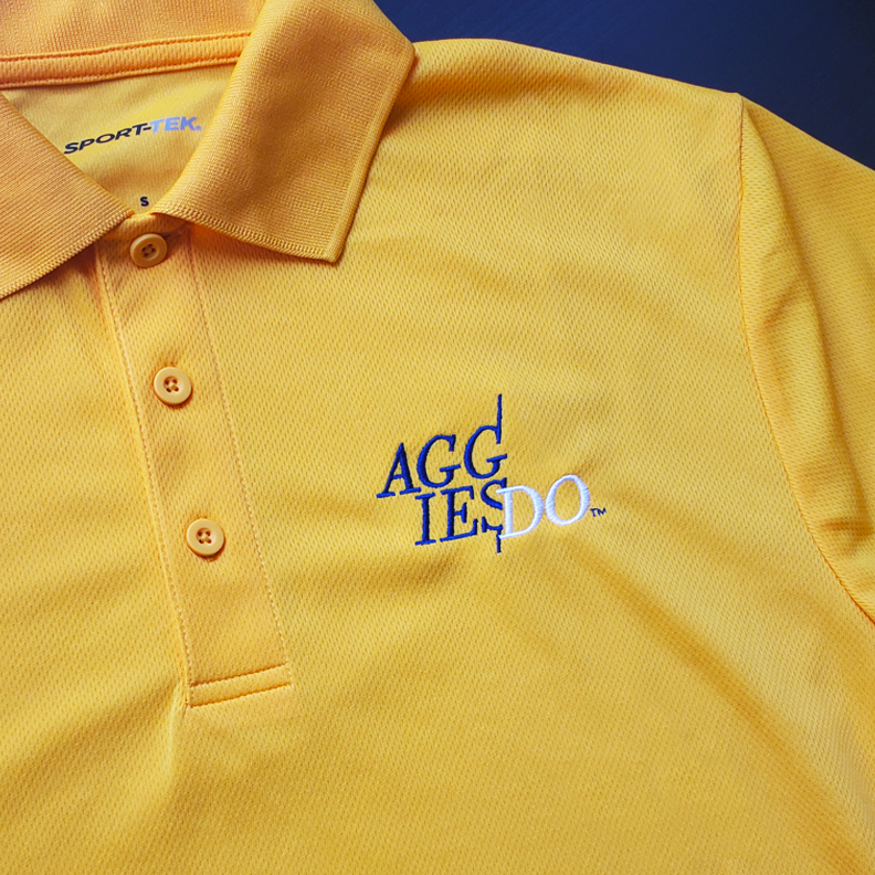 A yellow polo with the letters AGG IES DO embroidered on the breast.