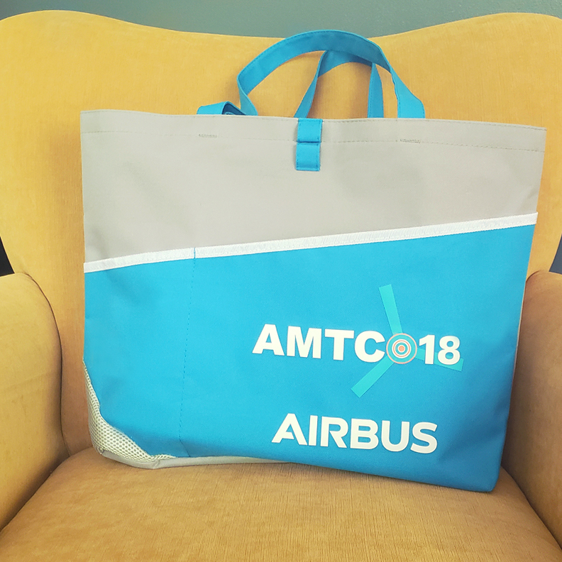 A large blue and gray carrying bag with 'AMTC 18 Airbus' printed on the front.