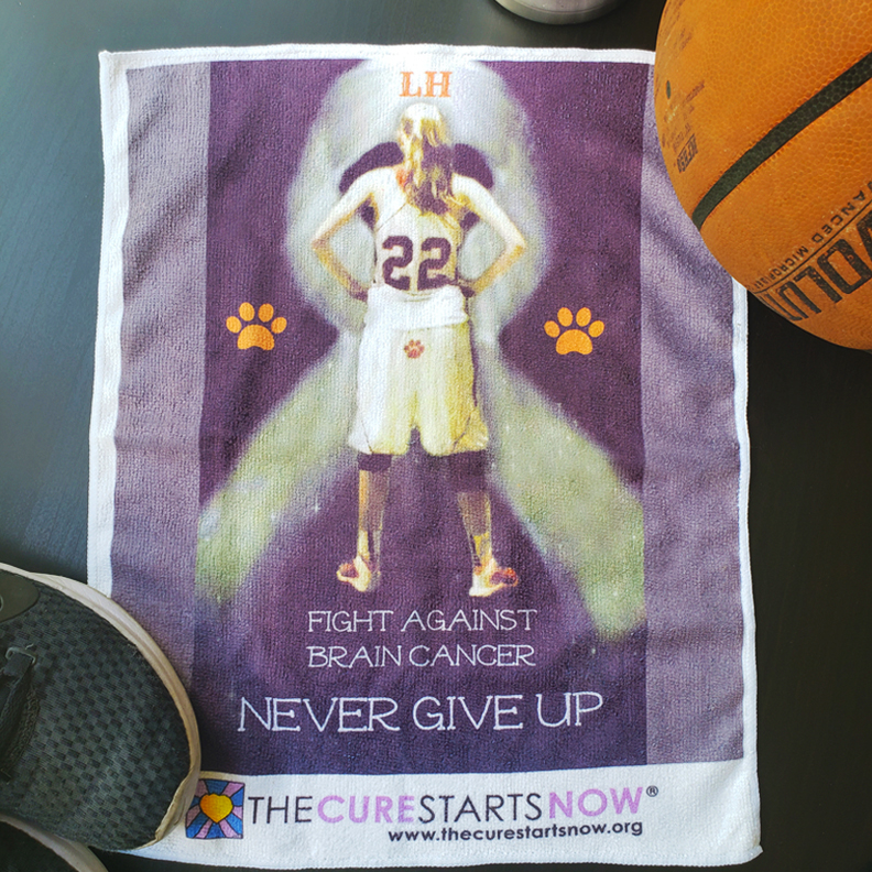 A towel with 'Fight against Brain Cancer, Never Give Up' on it. The Cure Starts Now logo is at the bottom. A female basketball player stands triumphantly with her back to us.