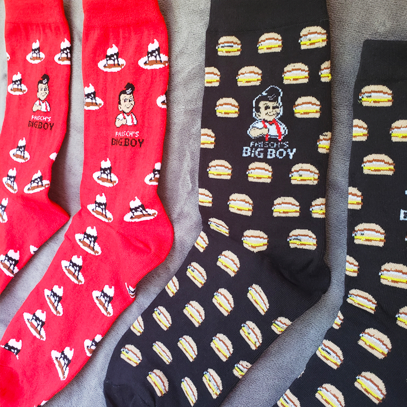 Two pairs of Frisch's Big Boy custom socks. One is red with fudge sundaes, the other is black with Big Boy burgers.