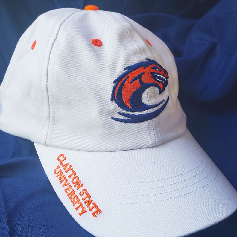 A white hat with Clayton State   University's mascot embroidered on the front. On the side of the bill, the words 'Clayton State University' is embroidered, too.
