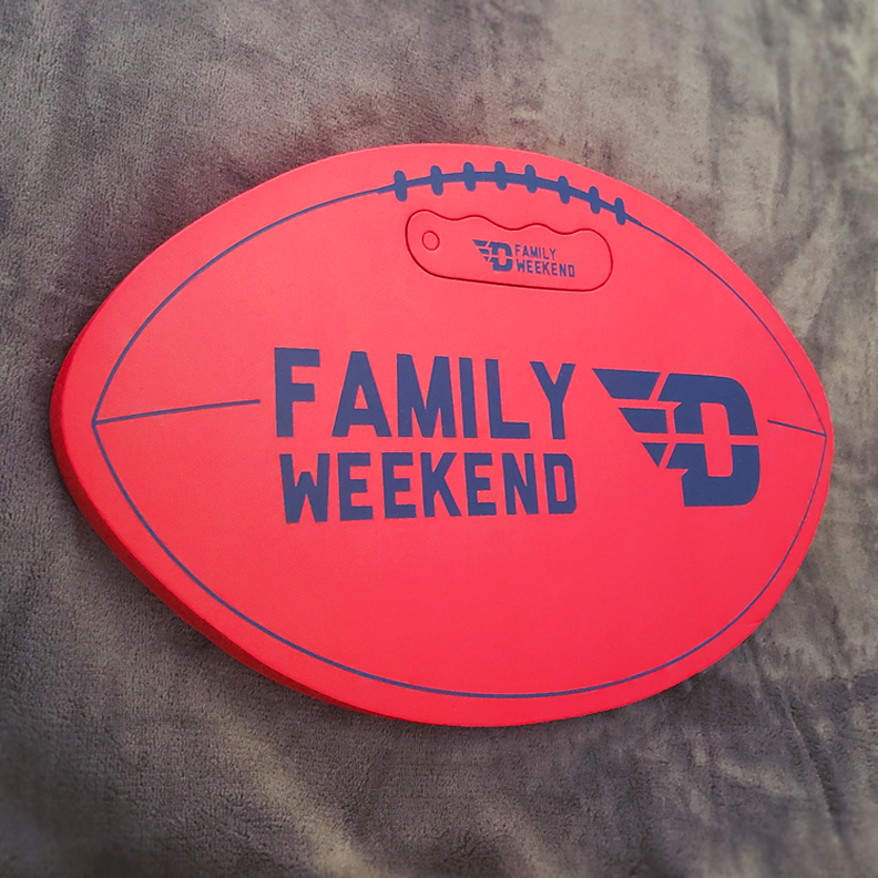 A red, flat foam football with blue text that says 'Family Weekend.'