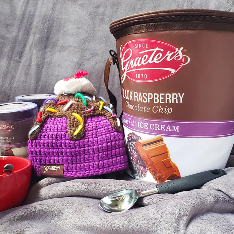 A custom Graeter's beanie boggin made to look like a sundae. Beside it is a cooler in the shape of a pint of ice cream made to look like a pint of Black Raspberry Chocolate Chip.