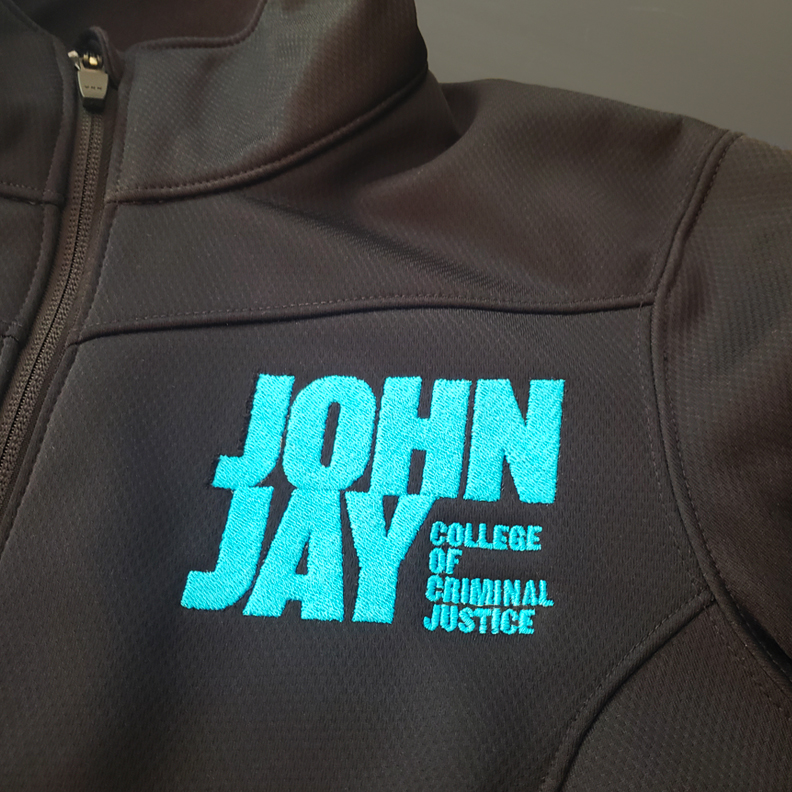 A zip up hoodie with the words 'John Jay College of Criminal Justice' embroidered in blue thread on the breast.