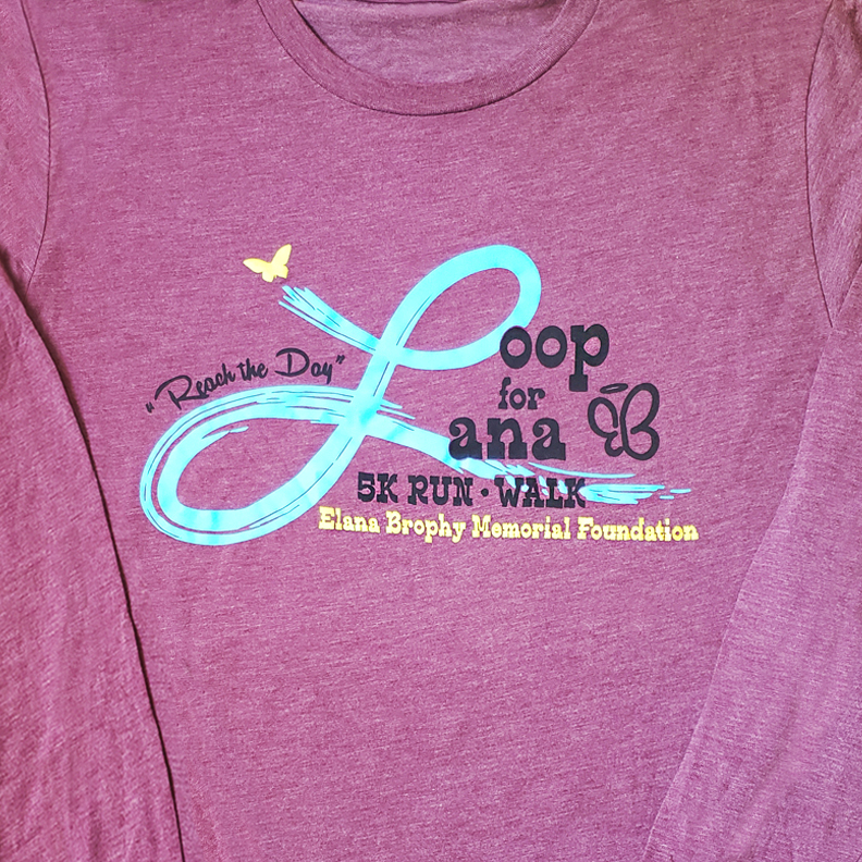 A red-violet shirt with the words 'Loop for Lana 5k Run and Walk. Elana Brophy Memorial Foundation' on the front.
