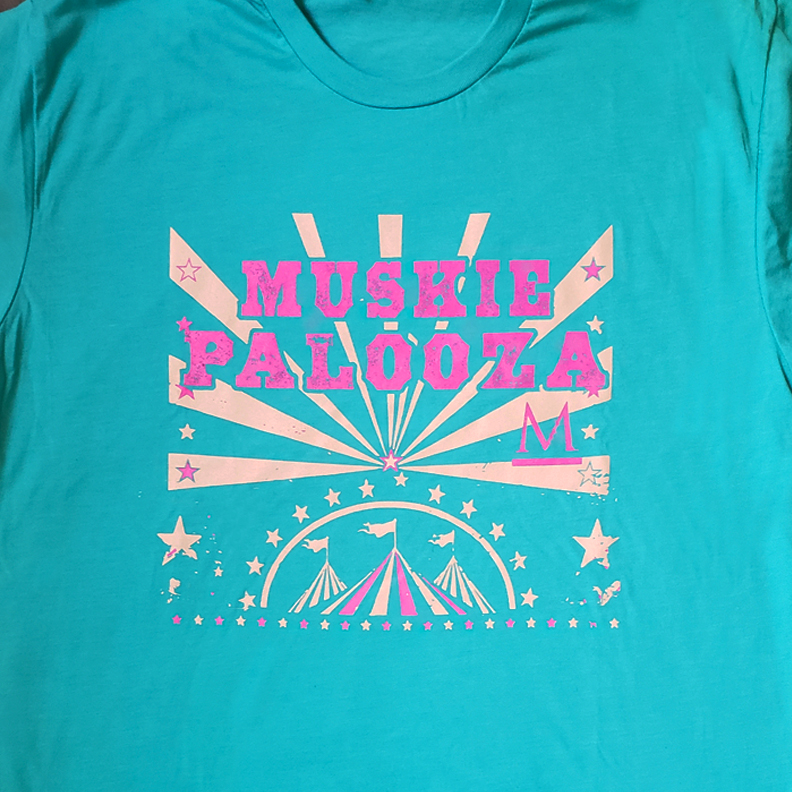 A teal shirt with the words 'Muskie Palooza' on the front. Pink and white circus tents, stars and light beams are beneath the words.