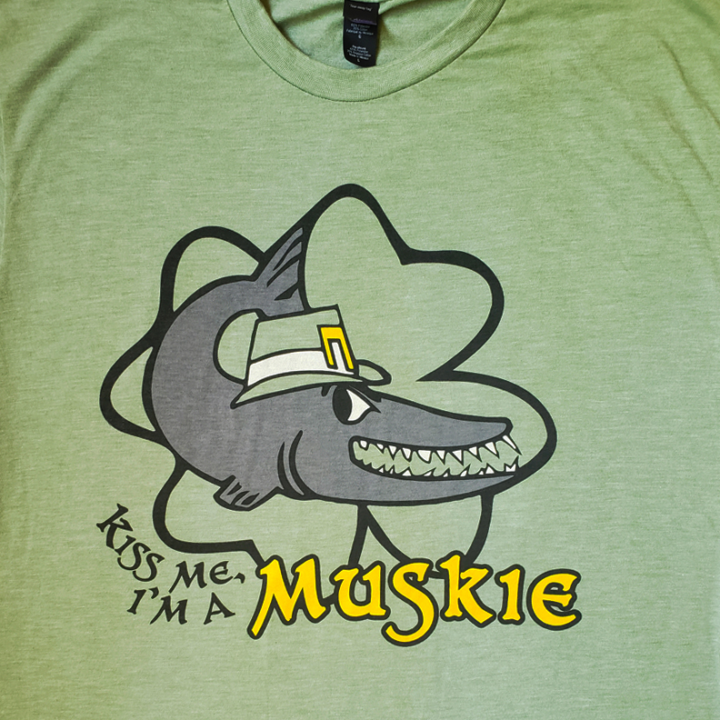 A green shirt with a muskie fish wearing a leprechaun hat. Underneath it says, 'Kiss me, I'm a Muskie.'
