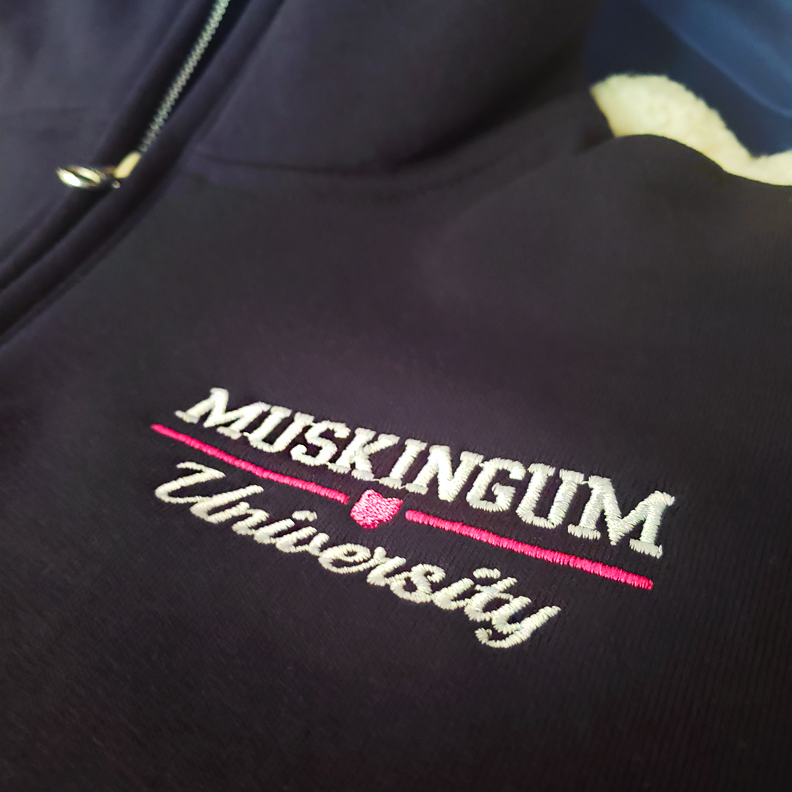 A pullover sweater with the words 'Muskingum University' embroidered on the left breast.