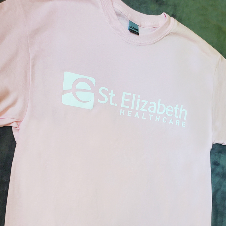 A pastel pink shirt with St. Elizabeth Healthcare's logo screen printed onto the front.