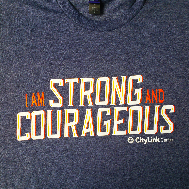 A blue shirt with the words 'I am STRONG and COURAGEOUS, City Link Center' screen printed on the front.