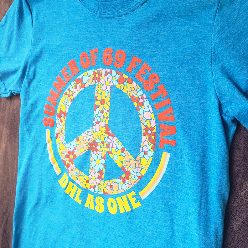 A blue shirt with a flowery peace sign in the middle. The text 'Summer of 69 Festival, DHL as One' encircle the peace sign.