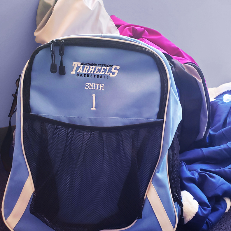 A periwinkle blue backpack with 'Northern Kentucky Tarheels, SMITH 1' embroidered on the front.