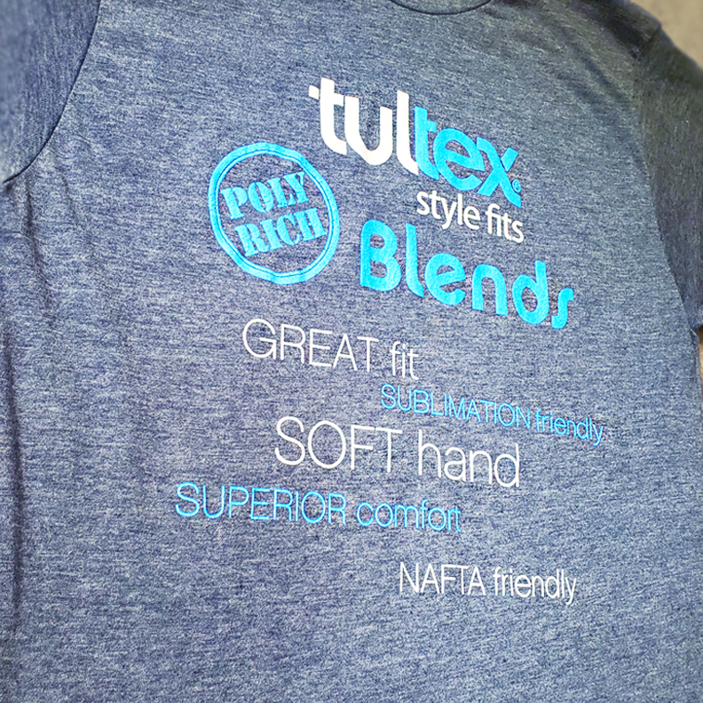 A blue gray shiet with the text 'Tultex Style Fits. Poly Rich Blends. Great Fit. Sublimation Friendly. Soft Hand, Superior Comfort, NAFTA Friendly' screen printed on the front.