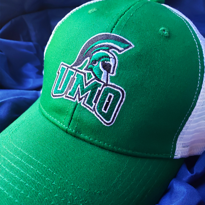 A green trucker hat with the UMO logo embroidered on the front.