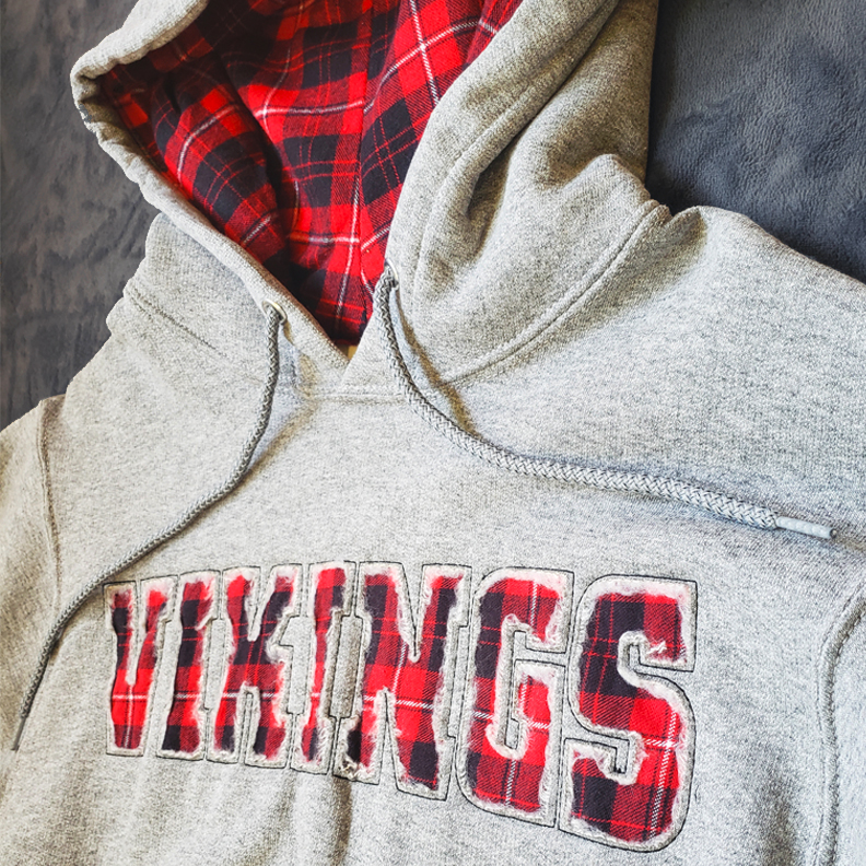 A gray pullover hoodie. The word 'Vikings' is cut out of the front. The words are filled in with a red tartan pattern. The inside of the hood also has the red tartan pattern.